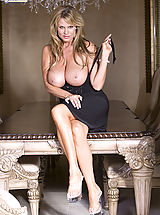 Huge Tits, Kelly wears a black dress and plays with her pussy on the dinning room table.